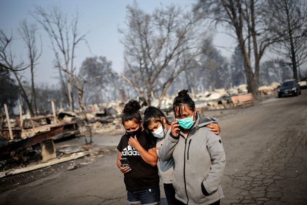 Sandra, Daniela, and Ester Reyes react while visiting their destroyed trailer home after the wildfires destroyed a neighbourhood in Bear Creek, Phoenix, Oregon