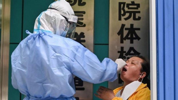 A medical worker takes a swab sample from a woman to be tested for the COVID-19 novel coronavirus in Wuhan
