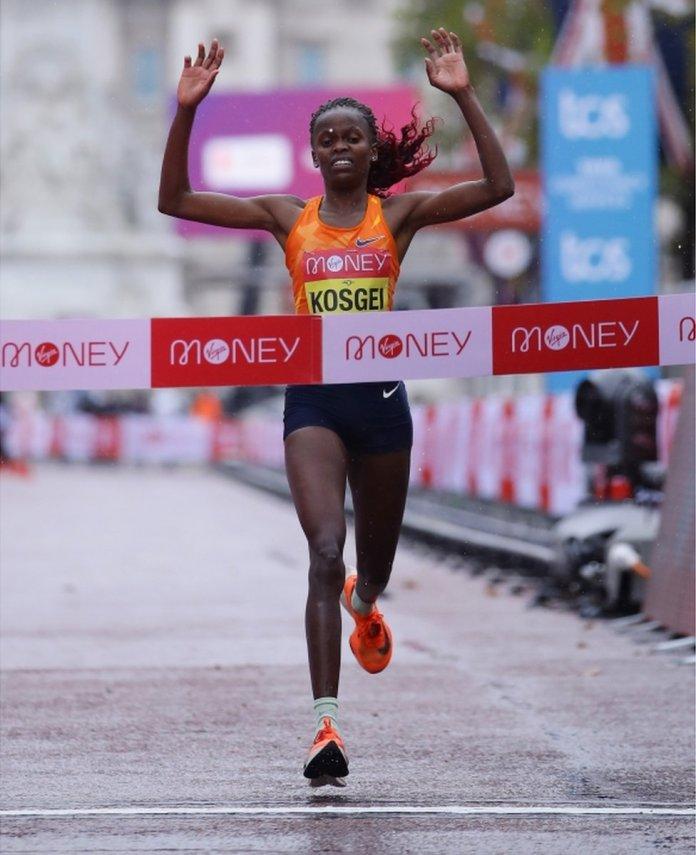 Brigid Kosgei raises her arms as she crosses the finish line.
