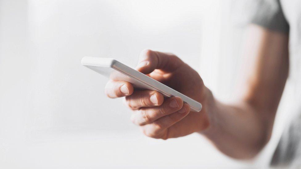 Persona con teléfono en las manos