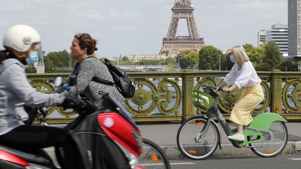 A woman wears a protective face mask while cycling across Pont Mirabeau bridge, near the Eiffel Tower