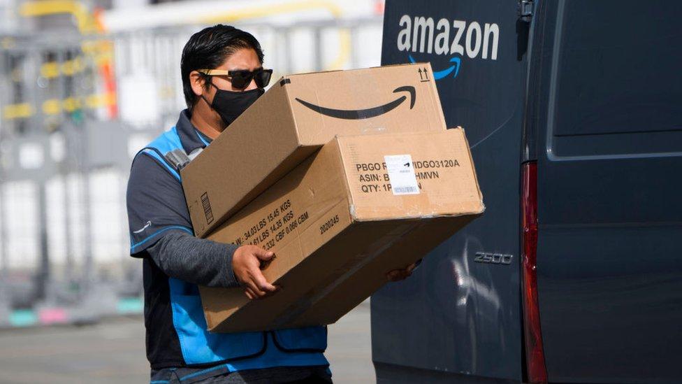 Trabajador de Amazon cargando unas cajas.