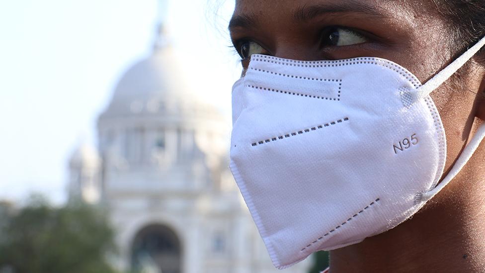 Una mujer con mascarilla en Kolkata, India