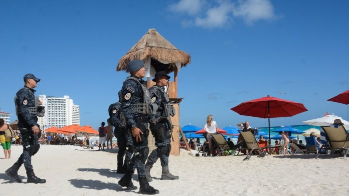 Federal police watch the beaches of Cancun.