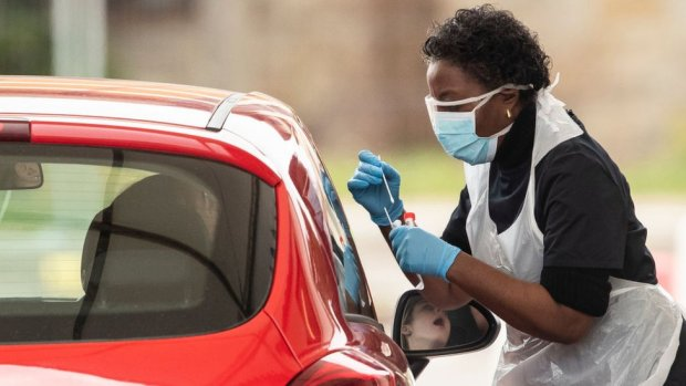 nurse administering covid test to driver in car