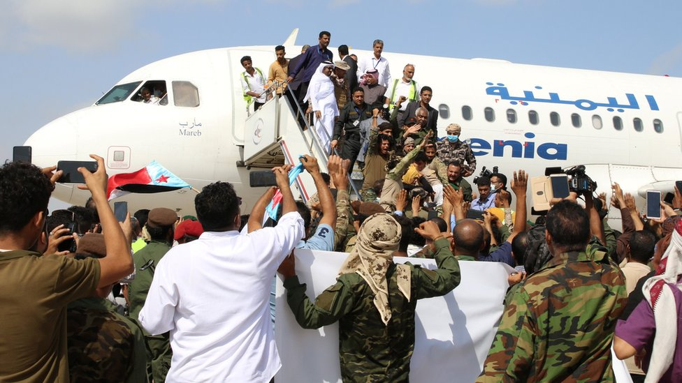 People take photos of passengers getting off a plane at Aden airport on 30 December 2020