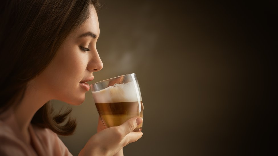 Mujer tomando café.