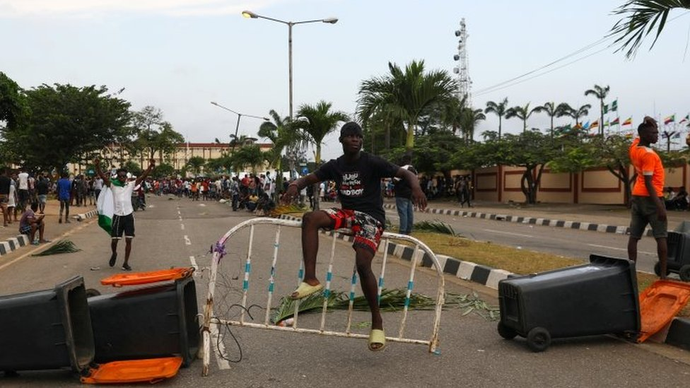 A protester sits on a barricade blocking a road in Lagos, Nigeria. Photo: 20 October 2020