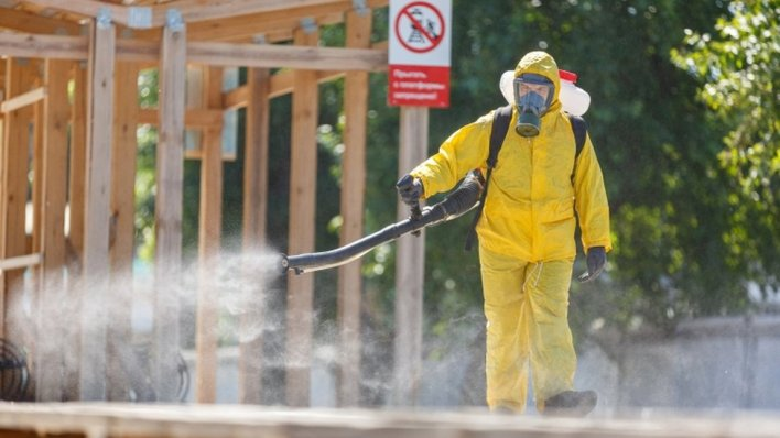 A specialist wearing personal protective equipment sprays disinfectant while sanitising a railway station in Moscow