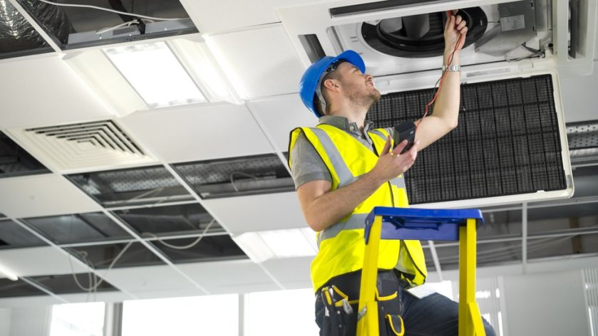 A workman fixing an air-conditioning vent