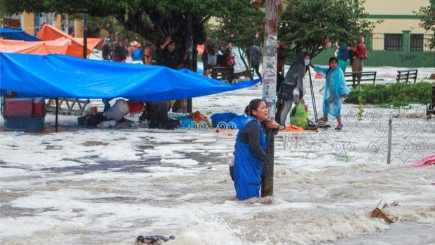 A woman clings to a lamp post during flooding caused by heavy rains in Sucre, Bolivia January 4, 2021