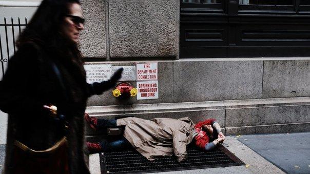 Una mujer pasa caminando cerca de un hombre sin techo en Nueva York.