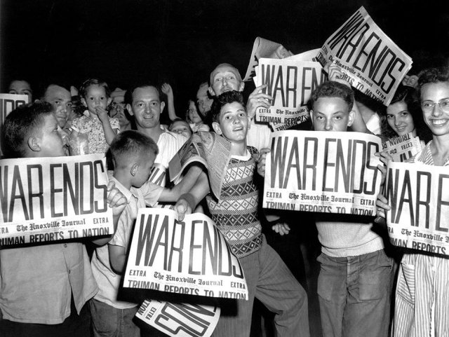 Children hold newspapers declaring the end of World War Two