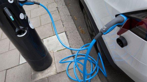 Auto eléctrico cargándose en una estación.