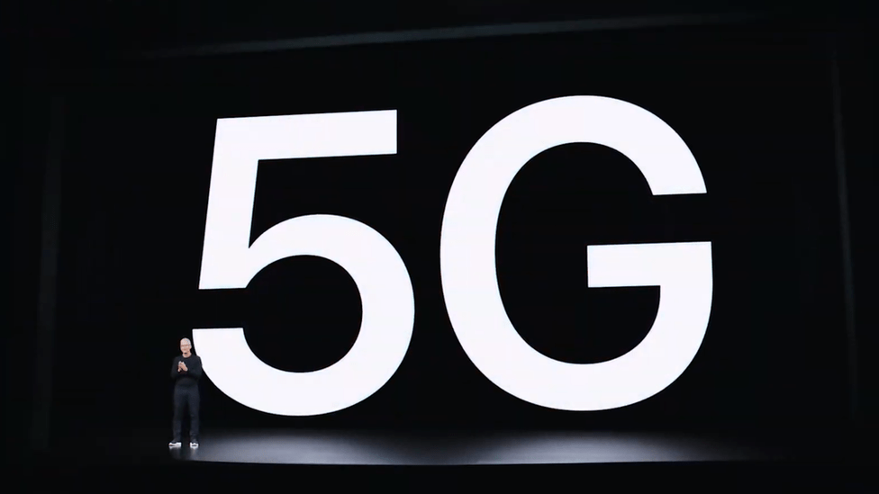 The letters 5G are displayed on screen behind Tim Cook on a huge dark empty stage