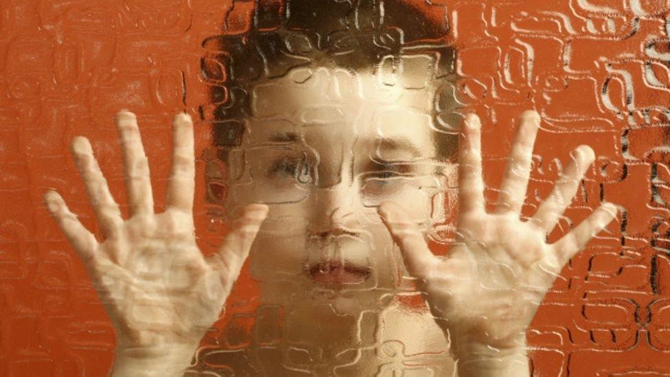 Niño detrás de un vidrio