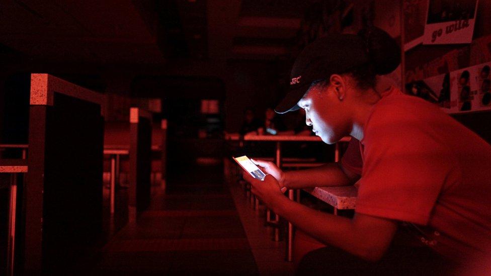 La empleada de un restaurante de comida rápida se ilumina con su celular durante un apagón.