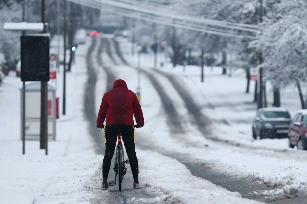 A cyclist rides down a snow covered road as heavy snowfall falls down on the West Midlands overnight on 28 December 2020 in Stourbridge, England