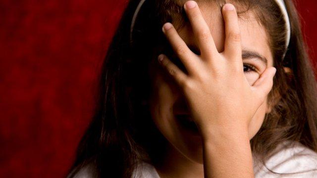 niña cubriendo su cara con la mano