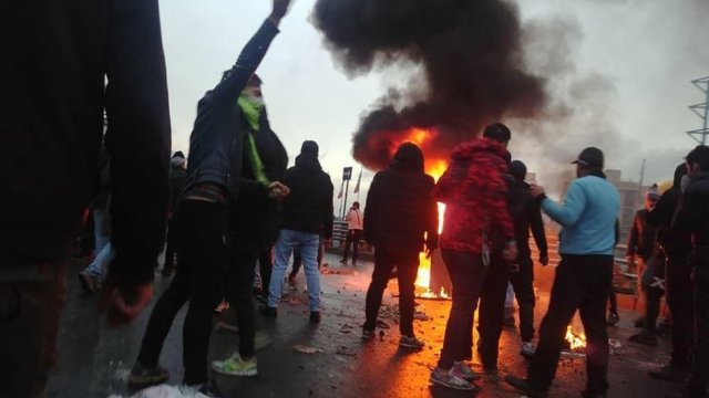 Iranian protesters gather around a fire during a demonstration against an increase in petrol prices in Tehran (16 November 2019)