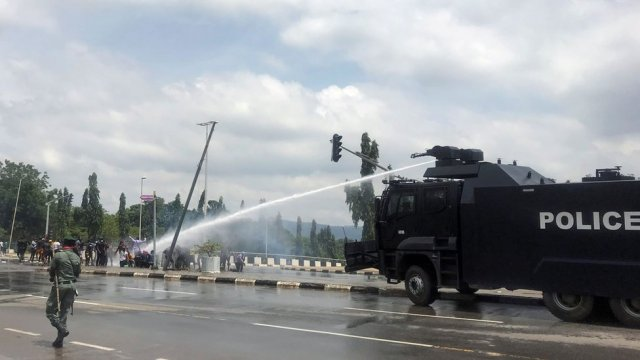 """Police use water cannons to disperse people protesting against alleged brutality by members of Nigeria""""s Special Anti-Robbery Squad (SARS), in Abuja, Nigeria October 11, 2020."""