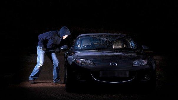 Un hombre intenta entrar furtivamente en un auto.