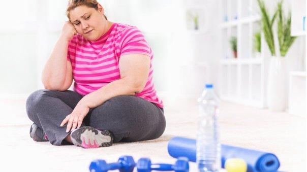 Una mujer sentada sin ganas de hacer ejercicio