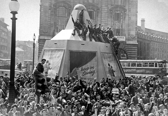 A crowd celebrates in Piccadilly Circus in London