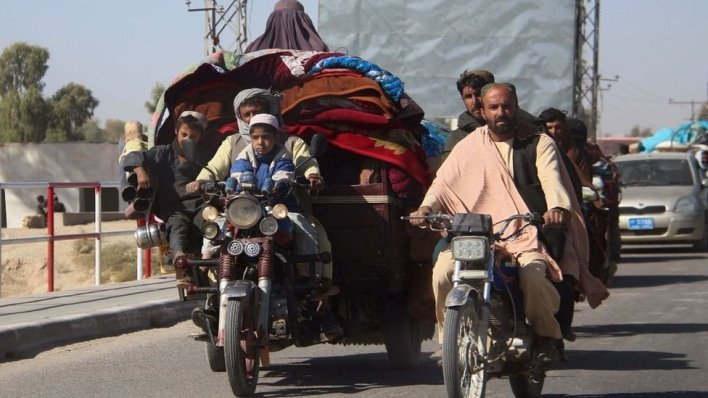 People on motorised vehicles heavily laden with carpets and blankets