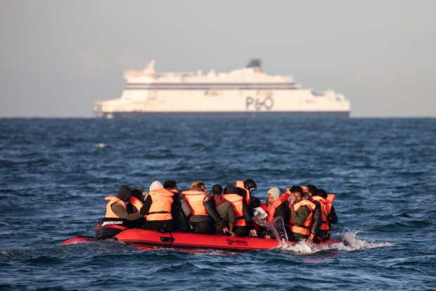 Migrants packed tightly onto a small inflatable boat bail water out as they attempt to cross the English Channel near the Dover Strait, the world's busiest shipping lane, on 7 September 2020 off the coast of Dover, England.