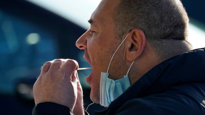 A man self-administering a coronavirus test