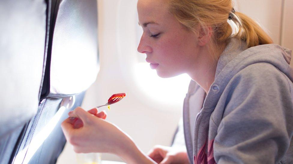 Una persona comiendo en un avión
