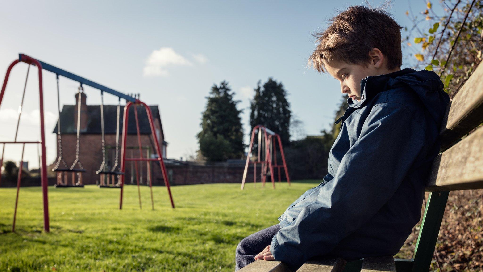 Niño solo sentado en un banco en el parque.