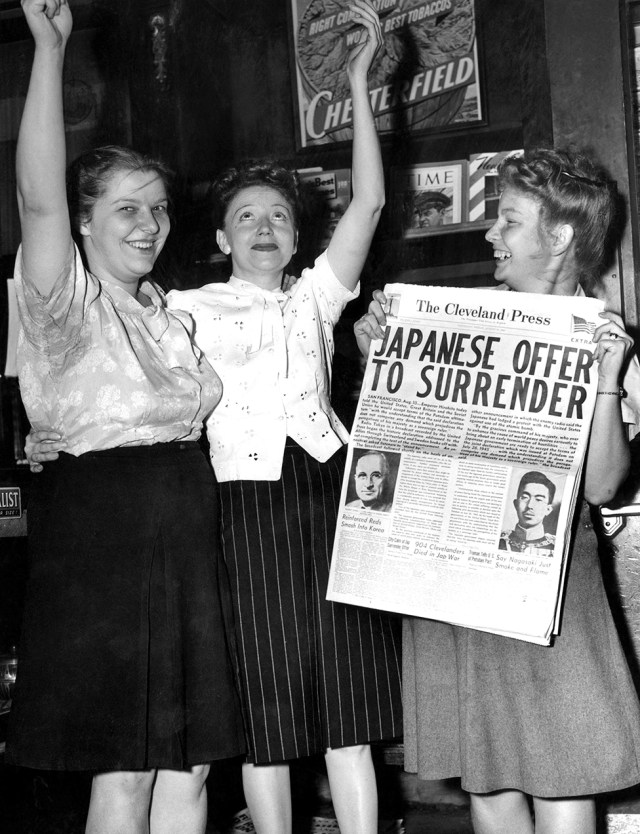 Women hold a newspaper and raise their arms