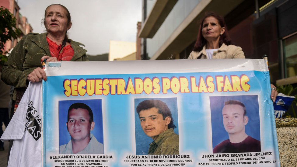 Women hold a banner with the portraits of three men kidnapped by the FARC guerrilla, during a protest outside at the Special Jurisdiction for Peace (JEP) headquarters in Bogota on July 13, 2018.