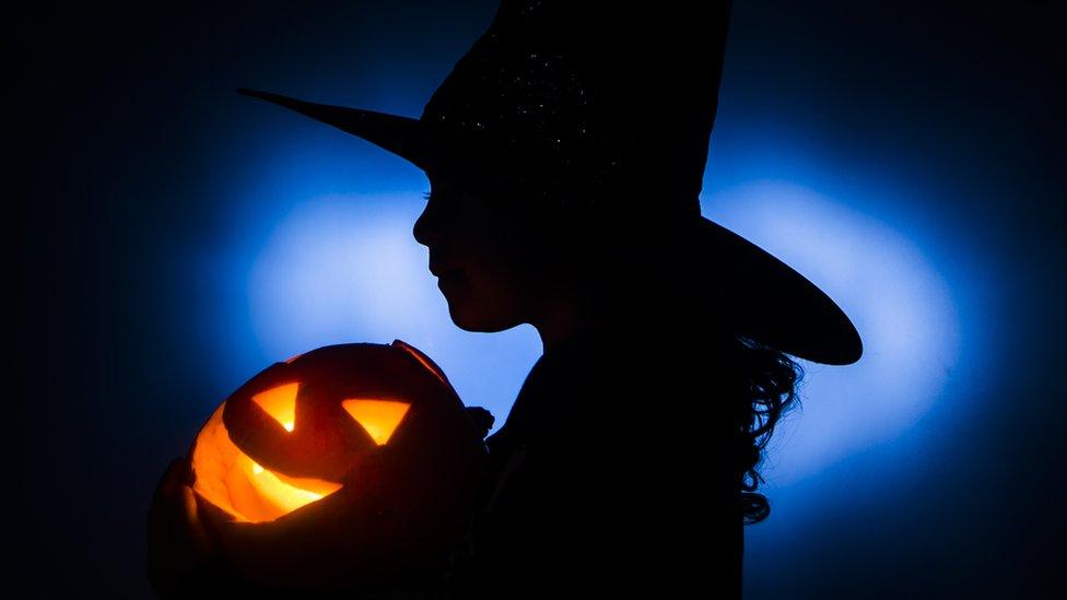Silueta de una niña disfrazada de bruja con una calabaza de Halloween