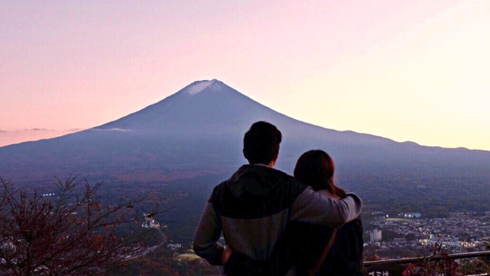 Couple embracing in a sunset watching a mountain in the distance