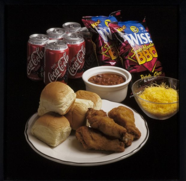 A meal featuring chicken nuggets, rolls, beans, crisps and cola