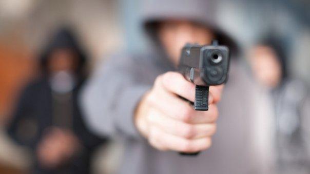 jóvenes apuntando con un arma