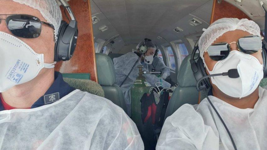 Pilotos aparecem à frente com paciente com oxigênio medicinal ao fundo dentro de aeronave
