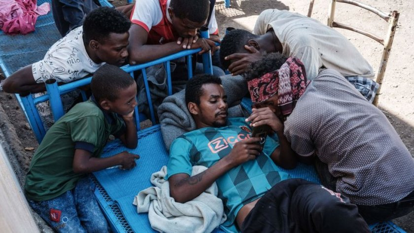 Ethiopian refugees gathering around someone's phone in Hamdayet, Sudan - 8 December 2020