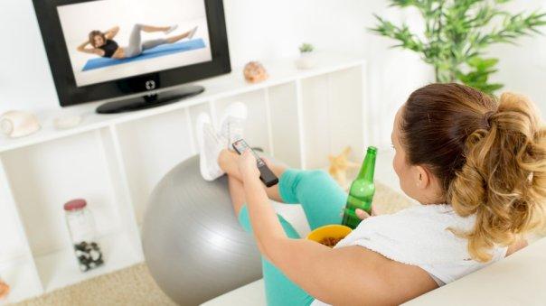 Una mujer viendo un programa deportivo con una bebida en la mano