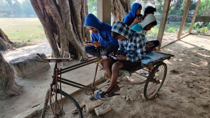 Children indulge in online gaming sitting on a broken down rickshaw.