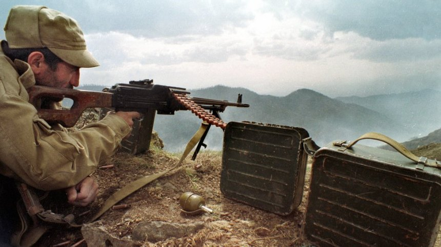 An Armenian soldier watches Azerbaijani troops on the frontline near the town of Hadrut, Nagorno-Karabakh (April 1993)