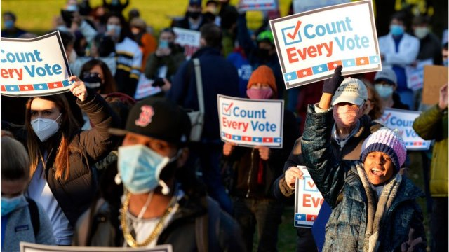 protesters holding signs saying every vote counts