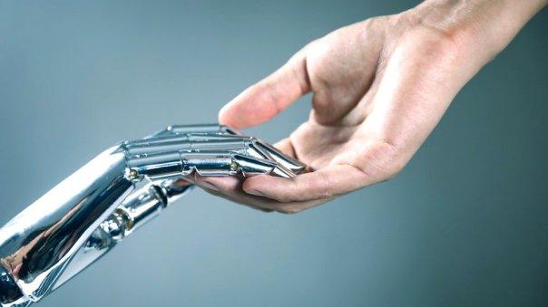 Imagen de una mano robótica y una humana uniéndose.