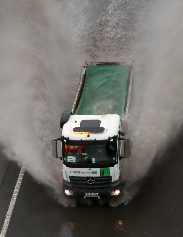 A lorry passes through a flooded road in Folkestone, Kent, on 14 January 2021
