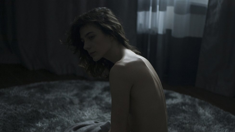 Una mujer desnuda en un cuarto oscuro