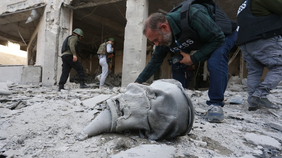 A photographer at the site of a damaged medical centre after alleged Azerbaijani shelling in Stepanakert in Nagorno-Karabakh, 28 October 2020