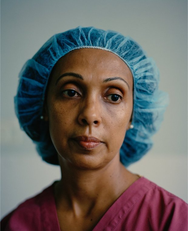 A portrait of an NHS frontline worker wearing scrubs